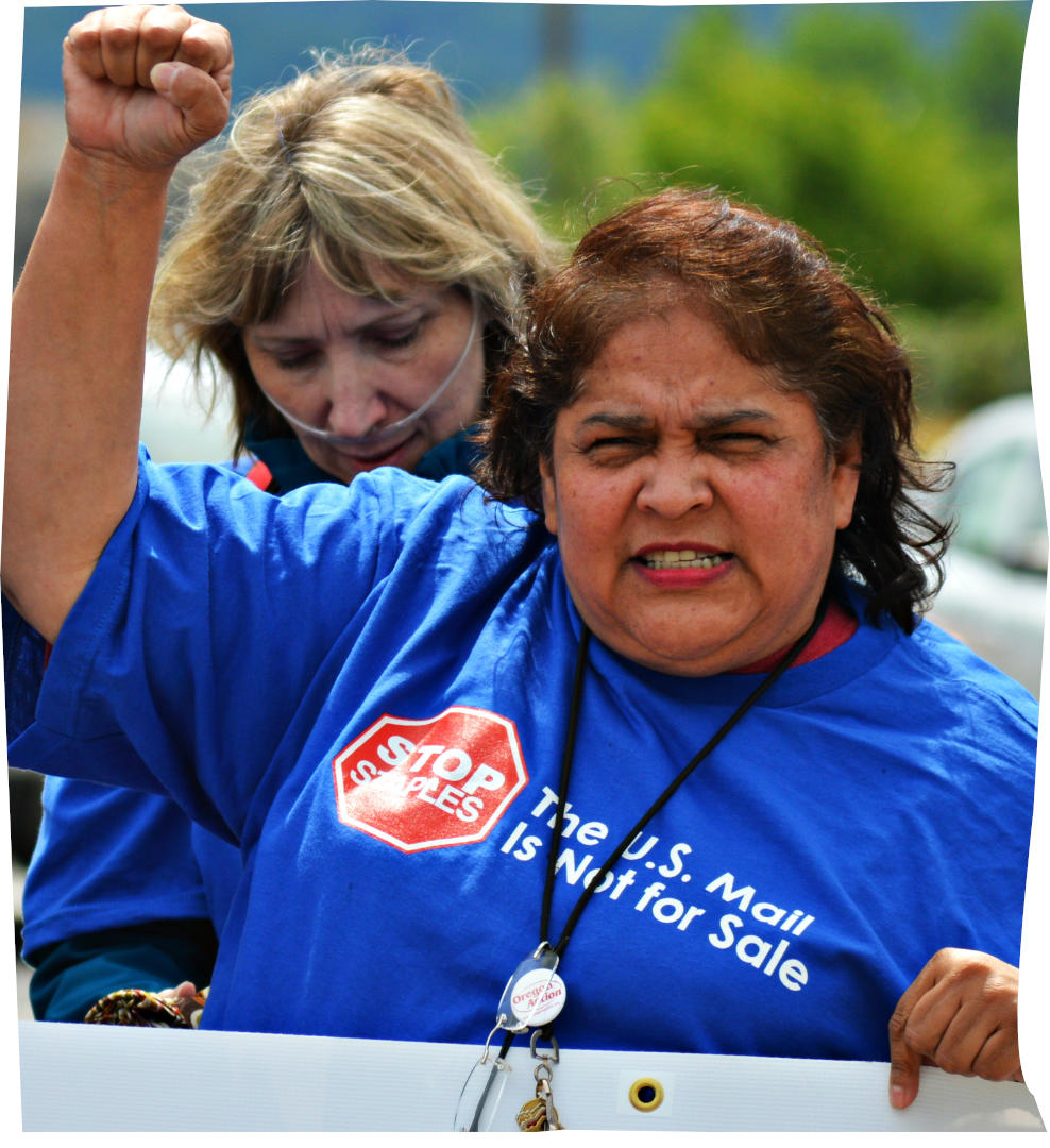 Woman in a blue shirt with a postal service slogan raising fist and holding a sign