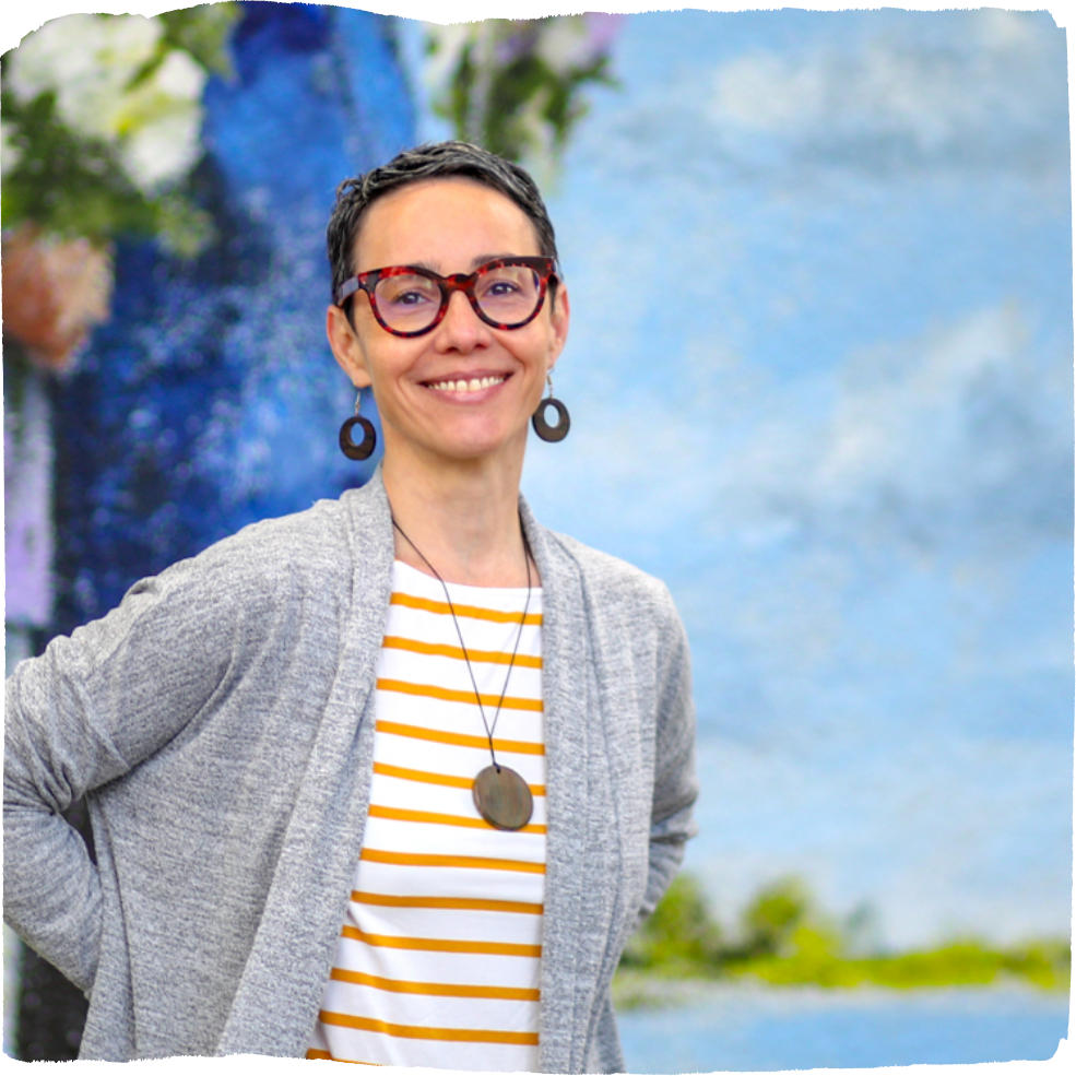 Violeta Rubiani, Director of Programs, wearing a striped shirt and grey cardigan standing in front of a light blue background.