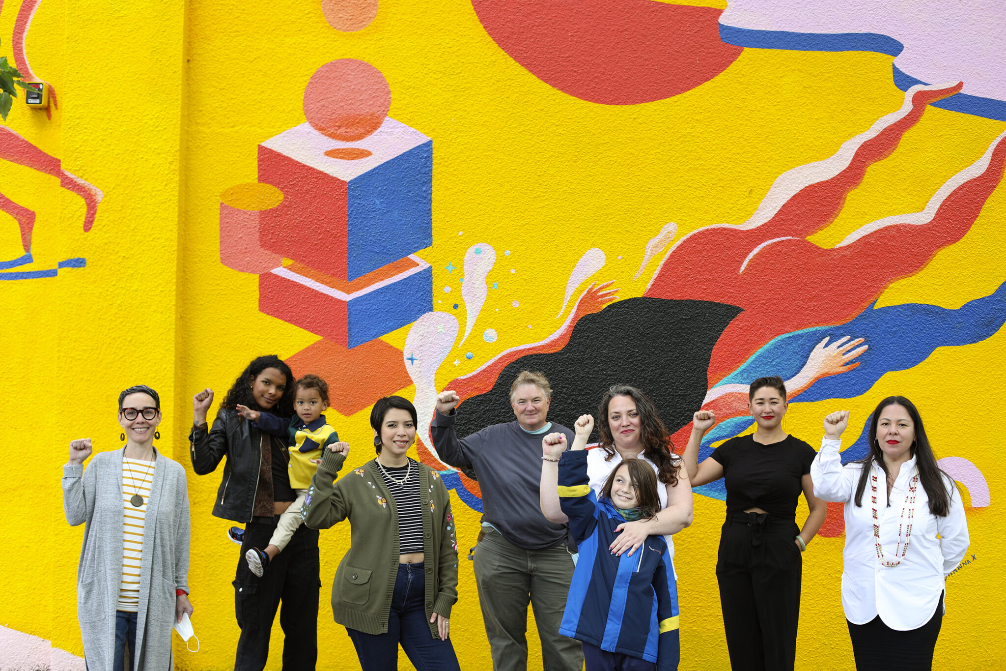 The Seeding Justice staff stand in front of a bright yellow mural with their fists raised up.