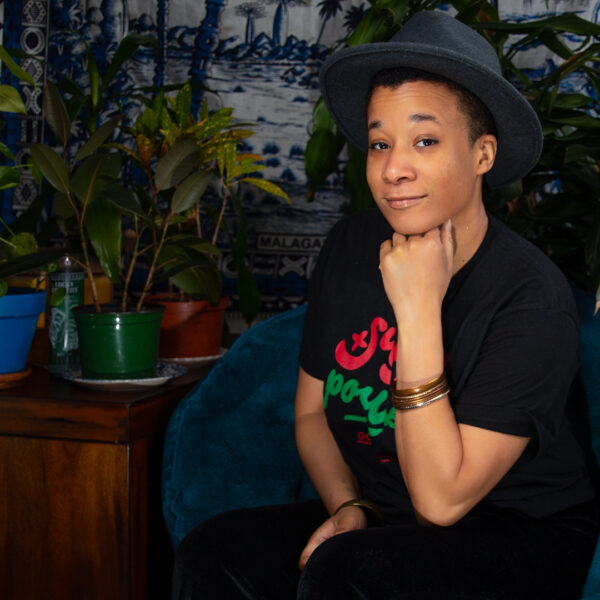 RaShaunda Brooks, in a hat, poses for a photo while sitting with her hand under her chin