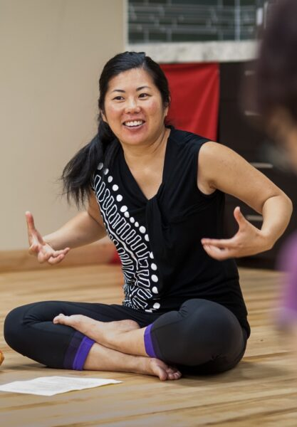 Michelle Fujii sits cross-legged on the floor, hands raised chest height and smiling as if getting prepapred.