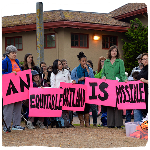 """A group of protestors holding pink signs that read, """"an equitable Portland is possible."""""""