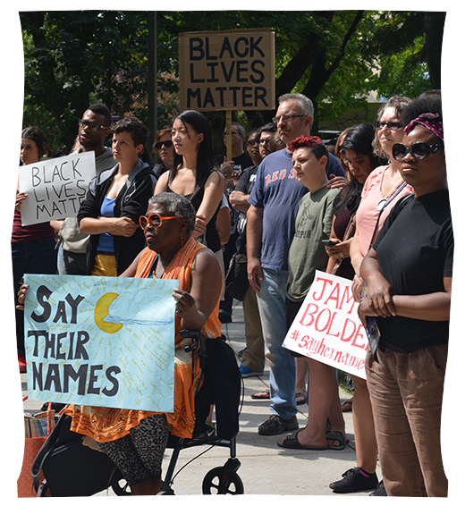 """A crowd holding protest signs with """"say their names"""" and """"black lives matter"""" stand quietly while listening to a speaker, out of frame."""