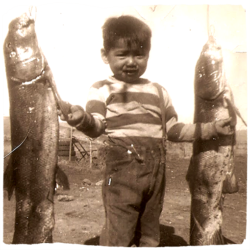 A child poses between two fish in an old, sepia-toned photo.